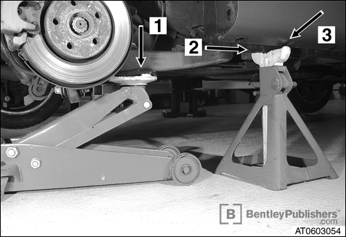 Proper positioning of floor jack and jack stand to safely lift vehicle. (BentleyPublishers.com watermark not printed on actual product.)