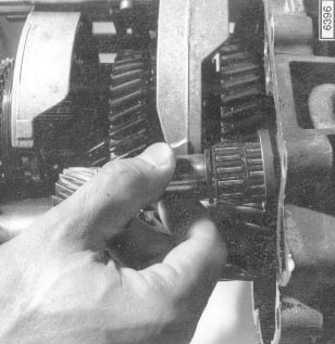 Fig. 7-7. Reverse gear shaft being withdrawn from transmission case.