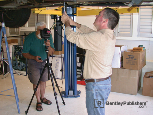 Bentley technical editors photographing fuel filter replacement.