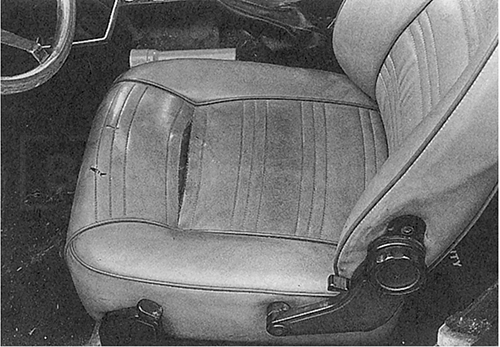 Fig. 3-15. Torn seat seams could be a result of brittleness caused by the car sitting in a hot place. Torn fabric gives opportunity to verify that material is plastic, not leather. Woven fabric backing indicates man-made material.