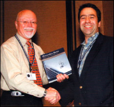 MBCA National President Richard Simonds (left) accepts a copy of the <b>Mercedes-Benz Technical Companion</b> at Startech 2005 from Bentley Publishers Editor Josh Davidson